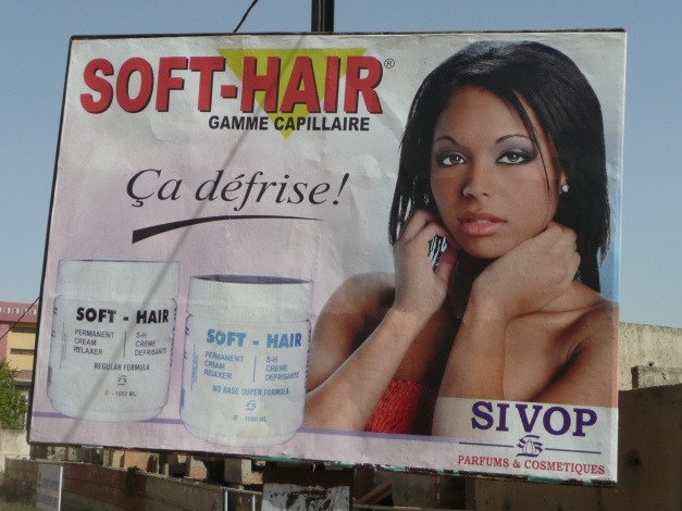 "An ad for hair straightener with a model who probably had straight hair to start with. Also some English words to add a bit of exotic ""cool"" in French speaking Burkina Faso"