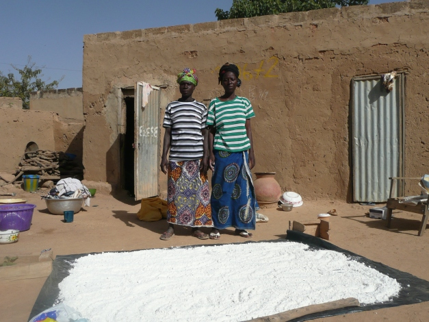 The wives (it's a Muslim family) in charge of drying out the maize flour. Toilet/shower combo on left of home