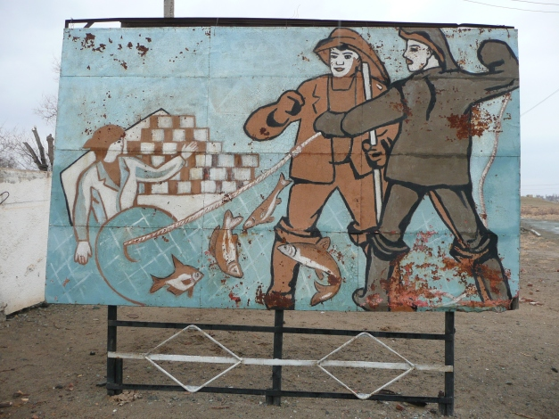Sign at the factory entrance depicting the noble toil of fishermen and can stackers