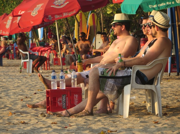 Typical beach users enjoying the finer points of Balinese culture