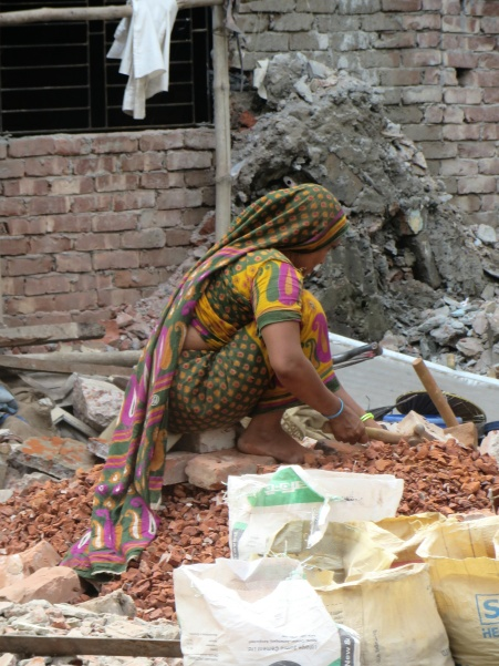 Women breaking bricks to make ballast for concrete is a comon sight due to the lack of suitable stone deposits in the country