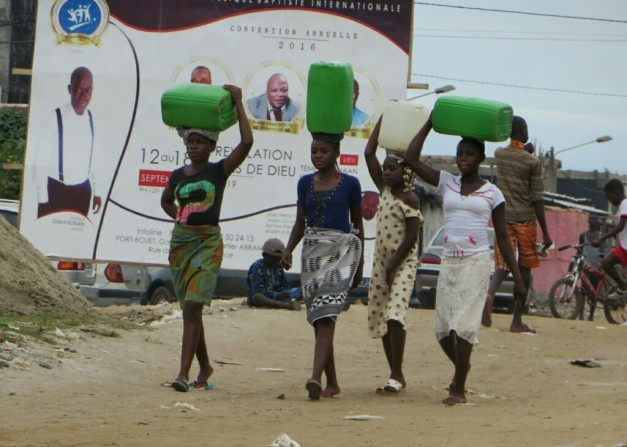Girls carry water back home, past an advert for one of the many local churches